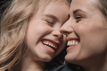 portrait of daughter and mother laughing on black