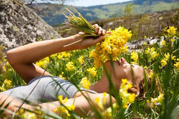 femme couchée dans l'herbe avec un bouquet de coucous
