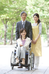 Senior man with wife in wheelchair and caretaker