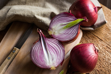 Red or purple onion cut in half, wood breadboard, linen towel, knife, kitchen table by window, rustic