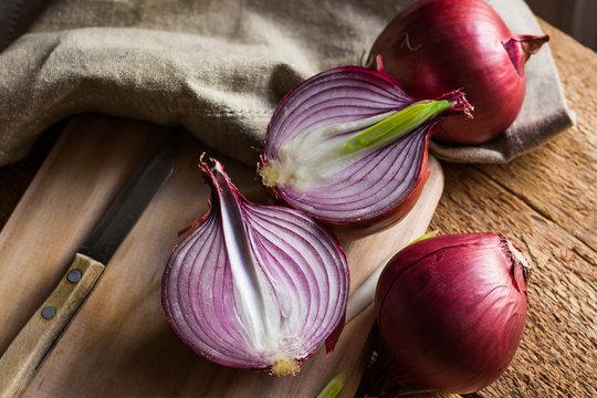 Red or purple onion cut in half, wood breadboard, linen towel, knife, kitchen table by window, rustic
