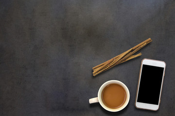 Cellphone and coffee on dark wooden background,top view