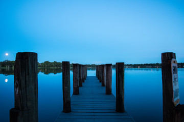 Night picture on pier at lake with moon and reflection
