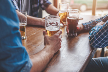 Hands holding glasses with beer on a table.