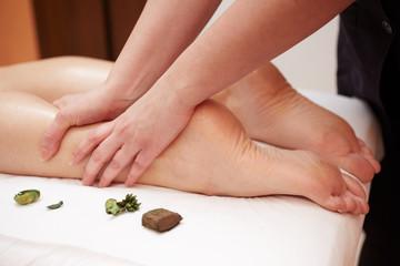 Detail of hands massaging human calf muscle.Therapist applying pressure on female leg