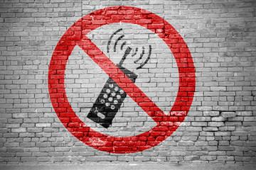 Ziegelsteinmauer mit Eingeschaltete Mobiltelefone verboten Graffiti