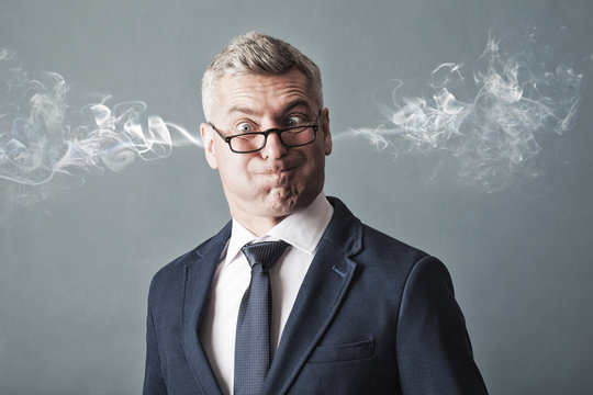 Closeup portrait of angry businessman, blowing steam coming out of ears