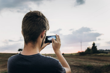 man holding phone and taking photo of amazing sunset landscape view in summer field. travel and vacation. exploring and discovering nature. instagram photography. space for text
