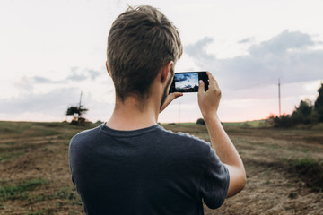stylish hipster traveler holding smart phone taking photo of beautiful sunset landscape in summer field. instagram photography. exploring and discovering. space for text.