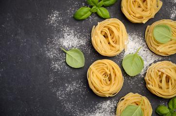 Raw tagliatelle pasta on the black concrete background, top view, copy space