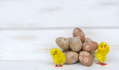easter eggs and yellow chickens  on a white wooden background