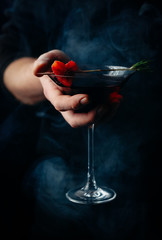 Mystical drink in a glass in a man's hand, decorated with an arrow from a sprig of rosemary and heart from a piece of bloody orange. Smoke, mysterious atmosphere, toned picture, close up