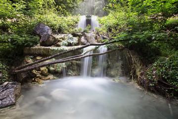 Sorgente termale di montagna immersa nel verde della foresta, fotografia in lunga esposizione