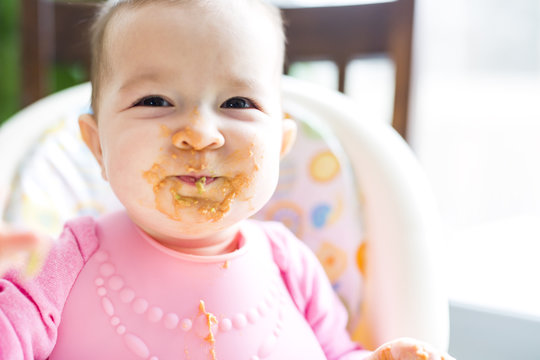 Adorable baby girl making a mess while feeding herself