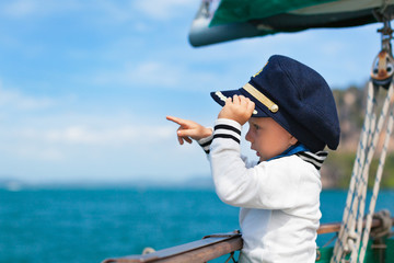 Funny little baby captain on board of sailing yacht watching offshore sea on summer cruise. Travel adventure, yachting with child on family vacation. Kid clothing in sailor style, nautical fashion.
