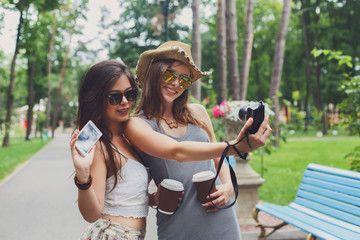 Happy tourists girl friends taking selfie photos