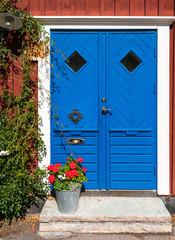 Wooden blue door and bucket with flowers, Kalmar, Sweden.