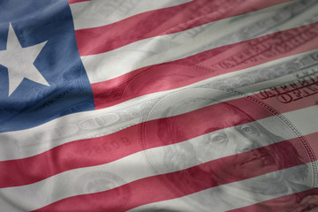 colorful waving national flag of liberia on a american dollar money background. finance concept