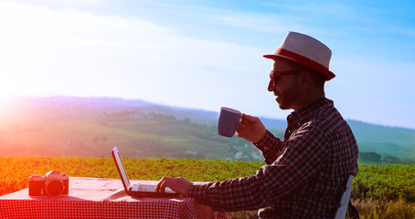 Creative man drinking coffee and working at laptop at sunset on countryside background - Silhouette of middle aged happy farmer relaxing with cup and pc at dusk light