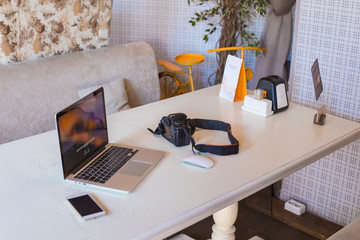 Laptop, phone, camera on a modern desktop.