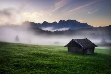 Geroldsee forest with beautiful foggy sunrise over mountain peaks, Bavarian Alps, Bavaria, Germany.