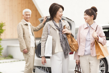 Family holding shopping bags, senior man standing by car, smiling