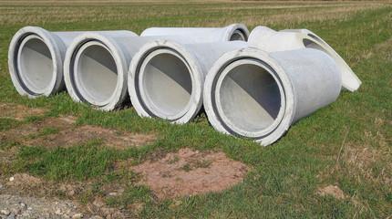 Betonrohre zum Bau der Kanalisation liegen auf einem Acker