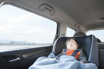 A boy sleeping in a car