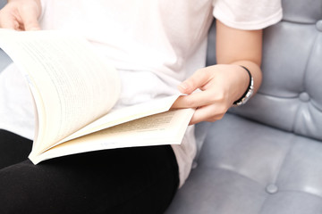 Girl sitting on sofa and reading book