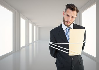 Businessman tied up in rope in corridor