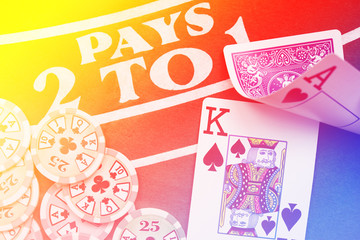 Blackjack playing cards hand on colorful background with chips stack