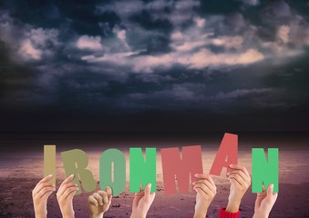 Hands holding word Ironman against stormy clouds