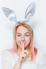 Pretty young woman with her finger in front of her lips while wearing bunny ears