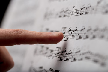 finger pointing to music score