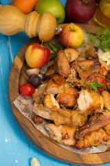 Whole roasted chicken garnished with tomatoes and apple on blue table.
