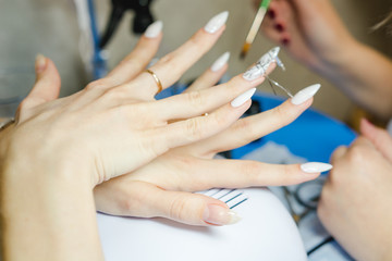 Manicure. The woman cleans and paints nails. The woman processes nails on hands a varnish. Shelak. Gel, a varnish, placing acryle on nails.