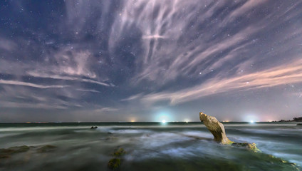 The beach at night with a rock toward the stars and sparkling galaxy create a great night scene to relax.