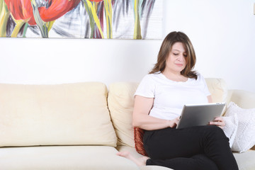 Woman relaxed on sofa using digital tablet.
