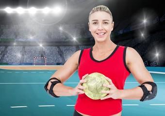 Athlete holding handball against stadium in background