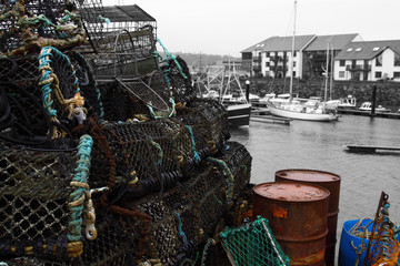 Lobster crab pots stacked on a quayside edited using selective colour