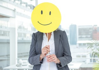 Businesswoman covering her face with happy smiley face