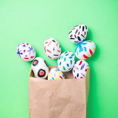 Easter eggs in a paper bag. Green background. Easter ideas. Easter eggs. Space for text.
