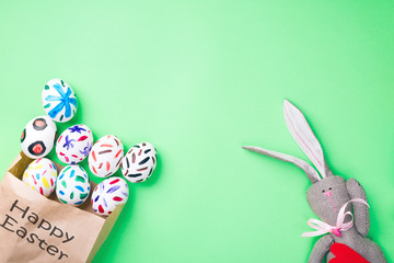 Easter eggs in a paper bag. Green background. Easter ideas. Easter eggs. Space for text. Black lettering on a bag happy easter.
