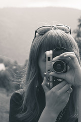 Outdoors portrait of a pretty young tourist taking photographs with vintage retro camera