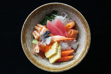 Sushi don , raw salmon tuna octopus and egg on rice