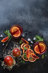Juice of blood oranges on a dark scratched metal background, top view with copyspace