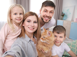 Parents with children and cat taking selfie at home
