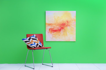 Pillow on red modern chair near green wall with abstract painting
