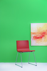 Modern red chair near green wall with abstract painting