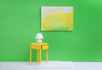 Lamp on little yellow table near green wall